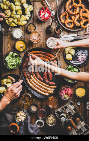 Flat-lay of Octoberfest dinner table with grilled sausages, pretzel pastry, potatoes, cucumber salad, sauces, beers and peoples hands with holding sna - Stock Photo