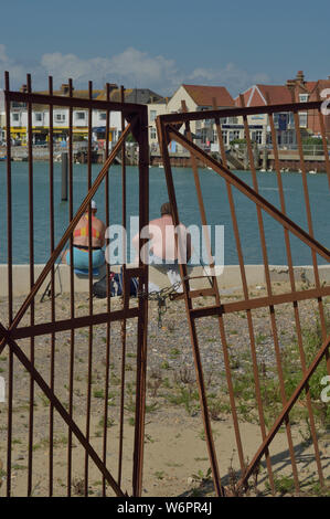 An overweight couple sitting on the waterfront. Littlehampton, West Sussex, England, UK - Stock Photo