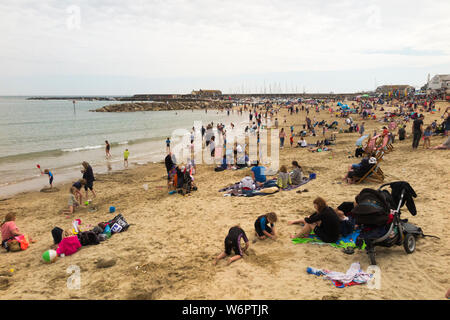 Lyme Regis sandy beach in spring / early summer on a warm grey day with plenty of holiday makers enjoying the sea and the sand. Lyme Regis, England UK. (110) - Stock Photo
