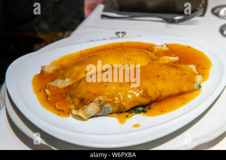 Vegetarian stuffed pasta noodle with red sauce served on top - Stock Photo