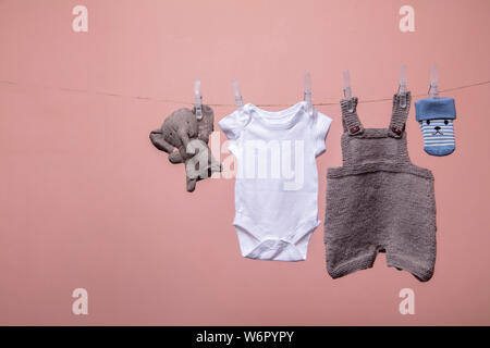 A set of cute newborn baby clothes and toys hanging on a line - Stock Photo