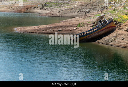 A shipwreck of a fishing boat on the bank of a river - Stock Photo