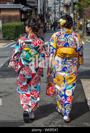 Two young Japanese women, wearing traditional kimonos, walking down a street in the Gion district, Kyoto, Japan - Stock Photo