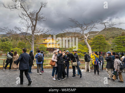 Tourists in front of Kinkaku-ji (Temple of the Golden Pavilion), Kyoto, Japan - Stock Photo