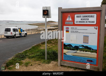 A car parked at Route submersible warning sign indicating that the road is liable to fllooding at high tide, Brittany, France - Stock Photo