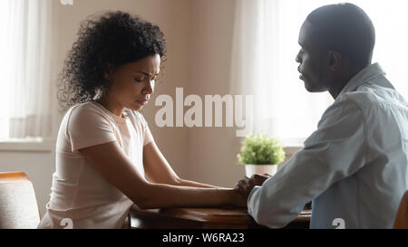 Spouses sit together holding hands loving husband soothing sad wife - Stock Photo