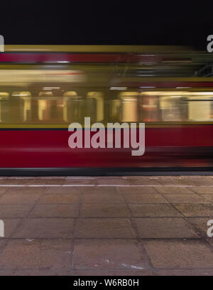 The train arrives in the night at the station in long-term exposure - Stock Photo