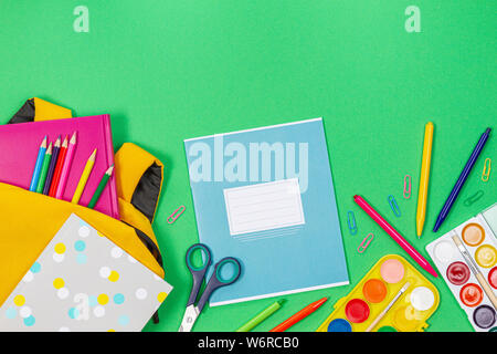 Back to school concept. Yellow backpack with school supplies and notebook on green background - Stock Photo