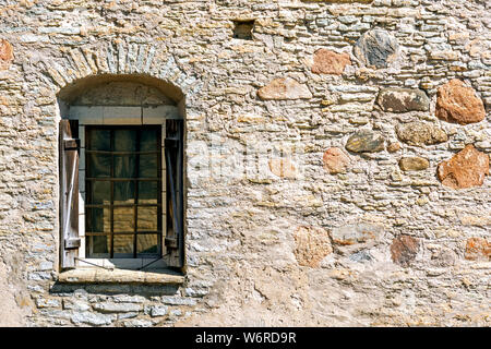 Window with arch, iron bars and wooden shutters on the fortress stone wall of the old castle in the city of Rakvere. From the window series of the wor - Stock Photo