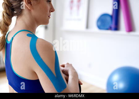Attractive blond woman in a bright sport therapy office with kinesio tape on her neck and shoulder to heal pain - Stock Photo
