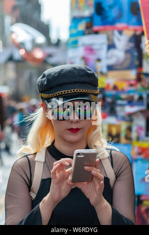 Edinburgh, Scotland, UK. 2nd August, 2019. A girl on the Royal Mile checking her mobile phone at the start of the Edinburgh Fringe Festival. Credit: Skully/Alamy Live News - Stock Photo