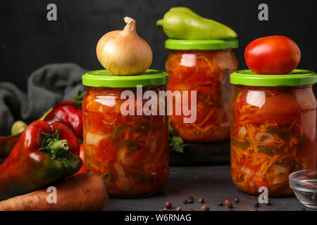 Vegetable salad in jars for the winter of tomatoes, carrots, onions and peppers, horizontal arrangement - Stock Photo