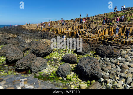 COUNTY ANTRIM, NOTHERN IRELAND - MAY 28, 2018: Tourists exploring Giants Causeway, an area of hexagonal basalt stones, created by ancient volcanic fis - Stock Photo