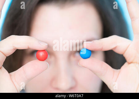 Woman holding pills in front of eyes - Stock Photo