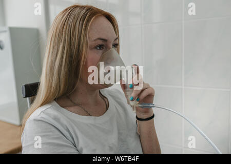 woman makes inhalation nebulizer at home  holding a mask