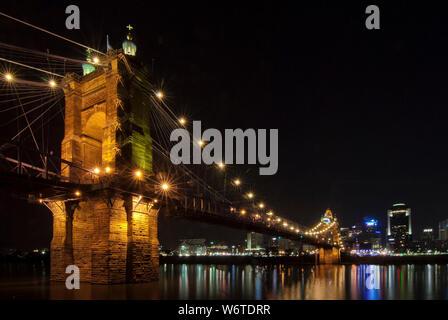 The John A. Roebling Bridge illuminated at night, spanning the Ohio River between downtown Cincinnati, Ohio, and Covington, Kentucky. - Stock Photo