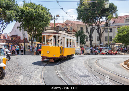 The famous yellow tram 28 passing in front of Santa Maria cathedral in Lisbon, Portugal - Stock Photo