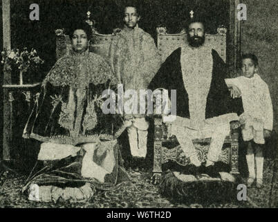 "This photo dates to the early 1920s. The caption reads: The Ruling Family of Abyssinia. His Imperial Majesty Haile Sellasi, ""King of Kings of Ethiopia, Conquering Lion of the Triabe of Judah, the Elect of God, and the Light of the World,"" claimed descent from King Solomon; with his wife, the Empress Menen, the Crown Prince Asfaou (center) and little Prince Makonen. The photograph was made in the Imperial Palace at Addis Adbeba, Ethiopia. - Stock Photo"