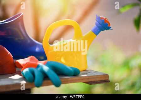 Gardening tools on wooden board with rubber boot garden gloves and watering can at back yard background - Stock Photo