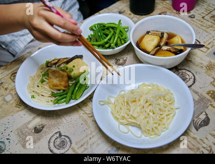 Japanese style udon noodles dipping soup with green beans, mushrooms, and tofu. - Stock Photo