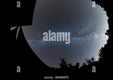 Sablet, The Vaucluse, France. 3rd August 2019. Clear dark skies in southern France show the Milky Way appearing brightly in the night sky above a village house. Credit: Malcolm Park/Alamy Live News. - Stock Photo