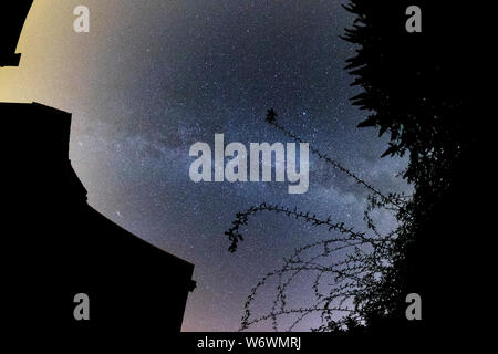 Sablet, The Vaucluse, France. 3rd August 2019. Clear dark skies in southern France show the Milky Way appearing brightly in the night sky above the garden of a village house. Credit: Malcolm Park/Alamy Live News. - Stock Photo