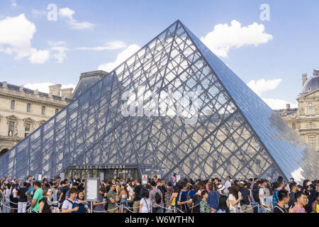 Louvre Paris overtourism - crowd of tourists queuing to enter the Louvre museum on a late afternoon in Paris, France, Europe. - Stock Photo