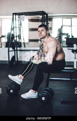 brooding male bodybuilder sitting on a bench after a workout in the fitness centre - Stock Photo