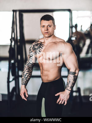 beautiful bodybuilder trainer showing off his body . photo with copy space - Stock Photo