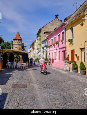 Sibiu, Romania, July 2019.  The colourful architecture of Cetatii Street in the old town featuring the carpenters tower and pedestrians - Stock Photo