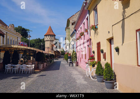 Sibiu, Romania, July 2019.  The colourful architecture of Cetatii Street in the old town featuring the carpenters tower - Stock Photo