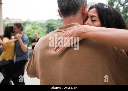 Barcelona, Spain - 10 july 2019: adult couple dancing tango with passion and huggin tight in outdoors park moving close to each other - Stock Photo