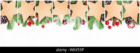 Christmas stars set. Empty wooden stars with green Xmas fir branch, red holly berries and baubles on white background - Stock Photo