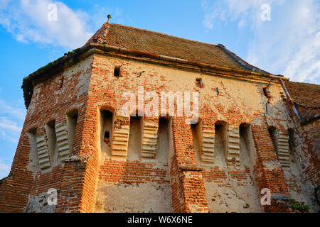 Alma Vii Fortified Church with warm sunset light. Popular touristic destination in Transylvania, Romania. - Stock Photo