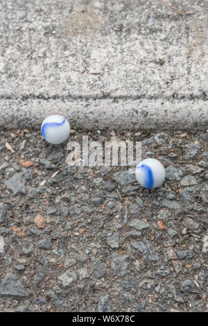 White glass marbles on kerbside tarmac surface. Metaphor something lost, mental health, losing your marbles, childhood games. - Stock Photo