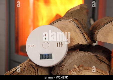 a CO detector in front of a burning fireplace - Stock Photo