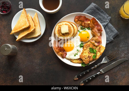 Full American Breakfast on dark, top view. Sunny side fried eggs, roasted bacon, hash brown, pancakes, toasts, orange juice and coffee for breakfast. - Stock Photo