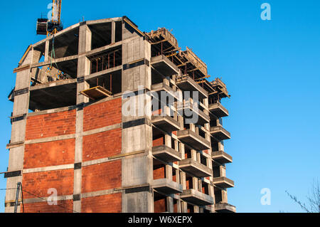 Residential contemporary building under construction in sunny day - Stock Photo