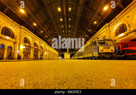 Ground view of the platforms at Keleti railway station in Budapest at night. Old trains at Keleti railway station in Budapest at night. - Stock Photo