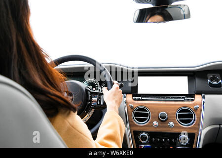 Woman hands holding car steering wheel of a modern car. Hands on steering wheel of a car driving. Girl driving a car inside cabin. Monitor in car with - Stock Photo