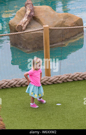 Bournemouth, Dorset UK. 3rd Aug 2019. Children and families enjoy the newly opened smuggler themed Adventure Golf Course, Smugglers Cove Adventure Golf, at Pier Approach. They wait excitedly to try out the new course and find out more about the smuggler theme on the first weekend following the official opening of the mini golf course on Wednesday 31st July. The use of the prime location on the seafront was controversial among locals with different ideas being proposed. Young girl playing mini golf minigolf miniature golf adventure golf putt putt. Credit: Carolyn Jenkins/Alamy Live News - Stock Photo