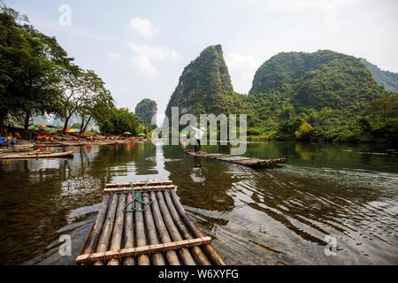 Punted bamboo rafting along the Yulong River, Yangshuo, China. - Stock Photo