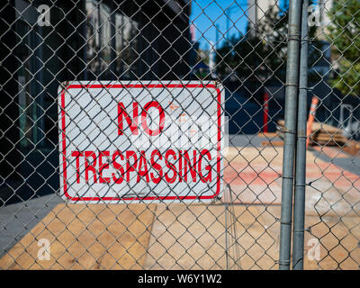 No trespassing sign behind fence wire in front of urban construction - Stock Photo