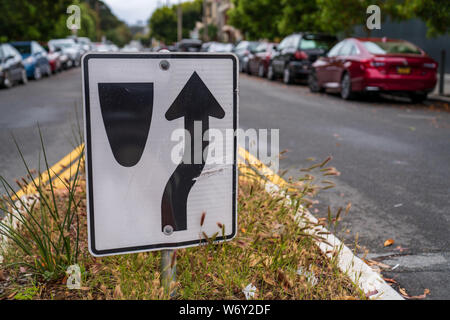 Traffic sign directing cars to go to right of median along crowded street - Stock Photo