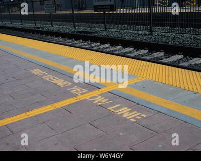 Wait behind yellow line warning on ground on train platform - Stock Photo