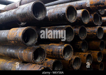 Oil Drill pipe. Rusty drill pipes were drilled in the well section. Downhole drilling rig. Laying the pipe on the deck. View of the shell of drill pip - Stock Photo