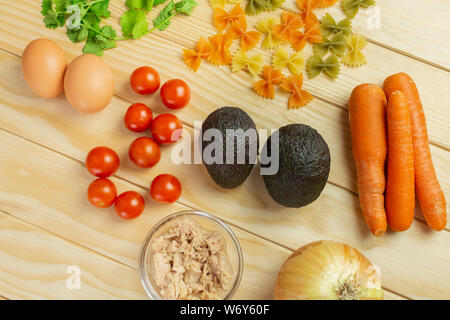 Onion, carrot, tuna, avocado, parsley, eggs, tomato and pasta, all fresh and organic ready to cook - Stock Photo