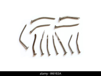 Deformed used metal nails on a white background. close-up photo - Stock Photo
