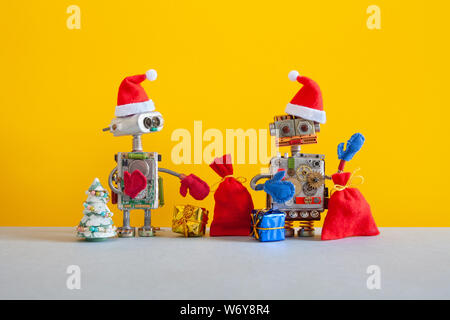 New Year Christmas party robotic greeting card. Two Santa Claus Robots with a bags of Xmas gifts on yellow gray background. Winter holidays poster - Stock Photo