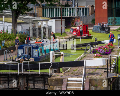 Regents Canal London - canal boats negotiate the historic St Pancras Lock, 1819, on the Regents Canal in the Kings Cross area of Central London. - Stock Photo
